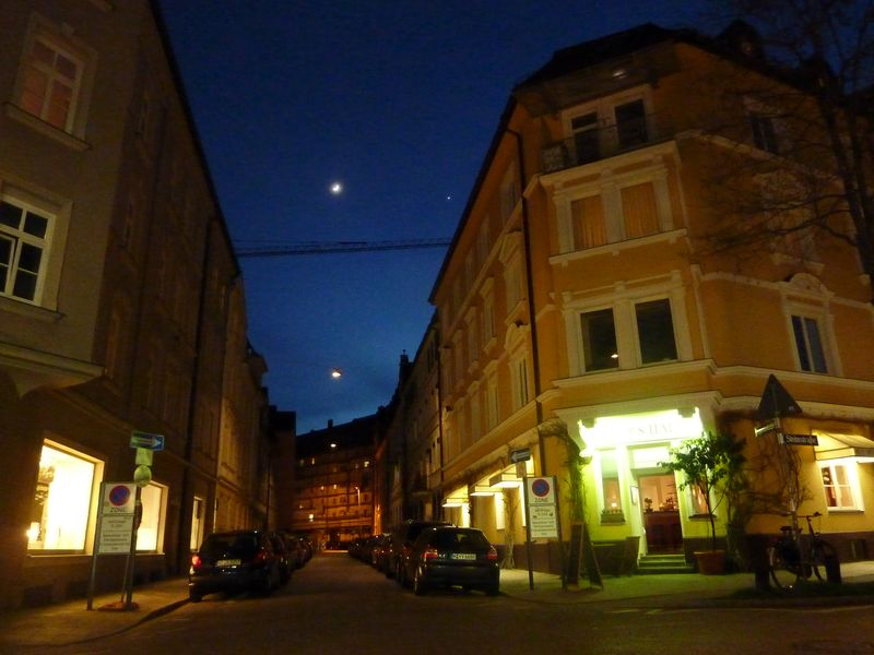 Quiet evening street in Munich with Venus and new moon